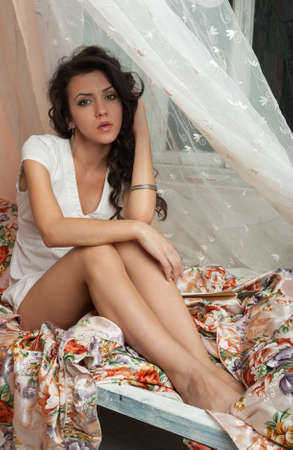 Gorgeous young brunette sitting on the bed and looking at the camera