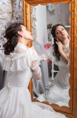 Young beautiful woman looking into a mirror, vintage style Stock Photo