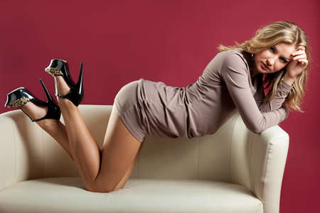 Portrait of a beautiful sexual young blonde woman on divan Stock Photo