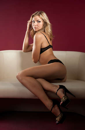 Portrait of a beautiful sexual young blonde woman on sofa in sexy lingerie Stock Photo