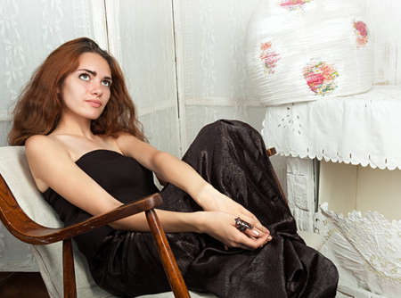 Portrait of attractive teenage girl in rocking-chair looking away