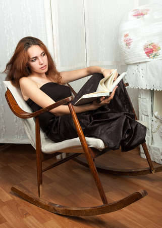 Portrait of attractive teenage girl in rocking-chair with book
