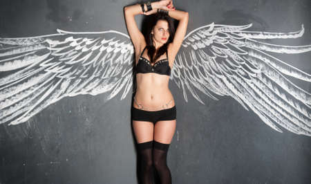 Gorgeous young woman in sexy black lingerie near wall with angels wing