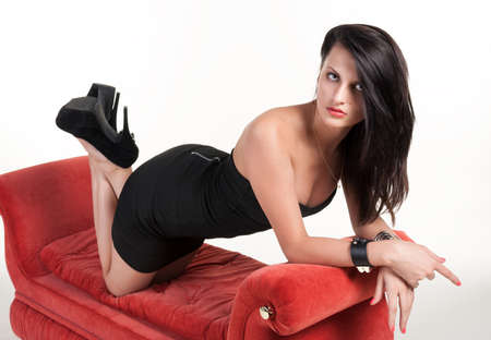 Beautiful young woman in black dress on red sofa looking at the camera