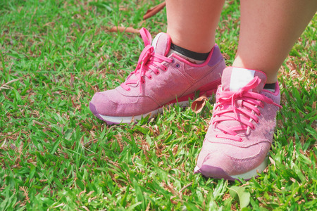 young girl feet: Pink sneaker on the grass in the park