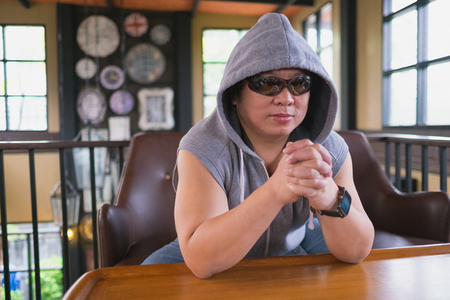 anorak: Man in gray anorak and sunglasses in hip-hop style sitting on sofa Stock Photo