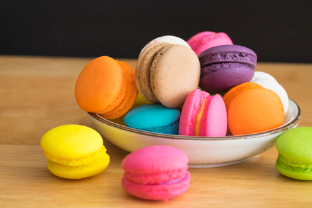 flavors: colorful macaroon in white ceramic plate with all flavors on wooden tablecolorful macaroon in ceramic plate Stock Photo