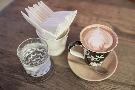 glass paper: hot coffee with tissue paper coffee on wooden table coffee and glass of water coffee near red sofa