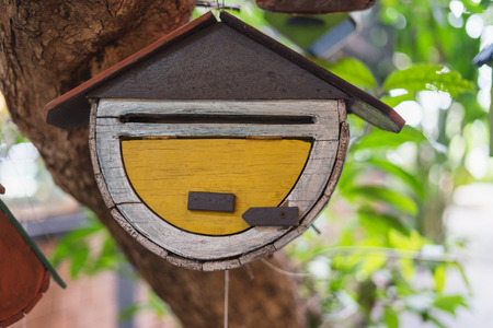 wooden birdhouse in brown yellow and white hang on tree surrounded green tree plant in the garden or park outdoor