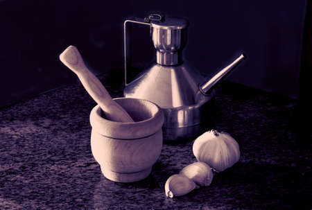 Ingredients of garlic sauce, vintage color, steel jug with olive oil, garlic head, garlic cloves, mortar and pestle
