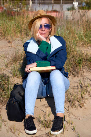 Woman sitting in the sun on the beach reading a book Banque d'images