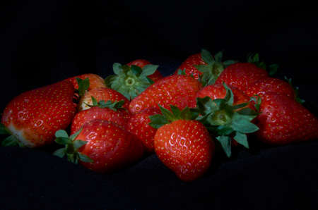Strawberries on black background, long exposure natural light