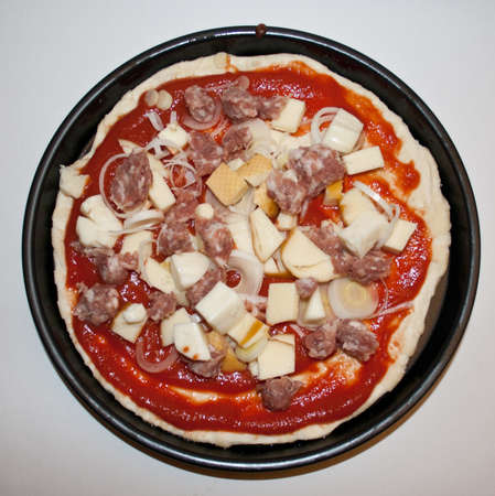 scamorza: pizza with sausage and scamorza before cooking. Picture from above on white background. Stock Photo