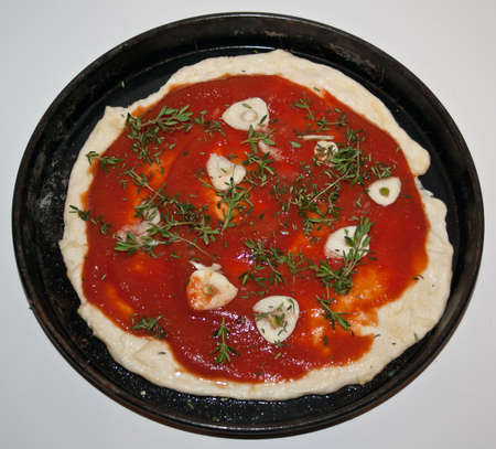 white backing: marinara pizza before cooking. Italian cooking recipe. On white background marinara pizza in black backing pan before ovening.
