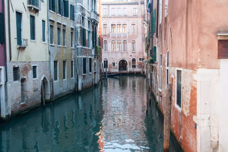 glimpse inside a channel in venice with incoming gondola and water reflections Imagens
