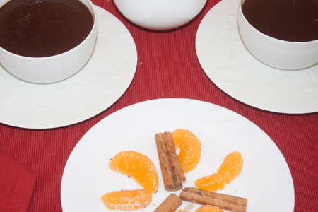 hot chocolade in cups on red tablecloth with orange slice and cinnamon garnish Stockfoto