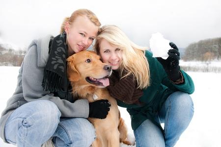 zwei junge Frauen mit Hund im Schnee