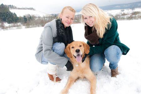 Freundinnen im Schnee mit Hund