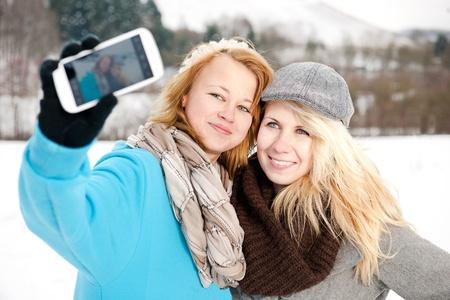 zwei Freundinnen fotografieren sich selbst mit einem Smartphone