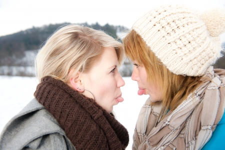zwei junge Frauen Strecken sich sterven Zungen raus