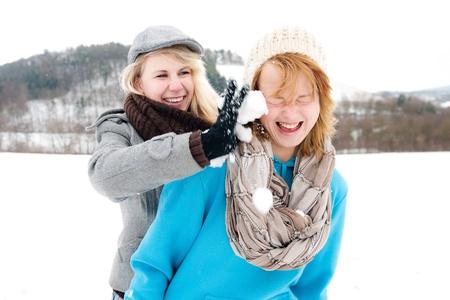 blonde Frau seift Freundin mit Schnee ein