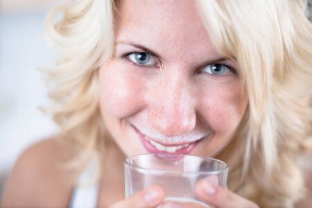 Young girl drinks a glass of milk in kitchen Stock Photo - 17718338