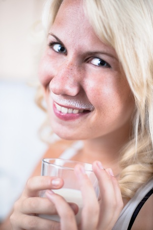 Young girl drinks a glass of milk in kitchen