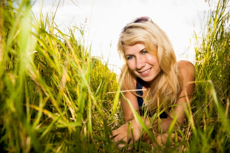 smiling young woman crawling through the tall grass Stock Photo