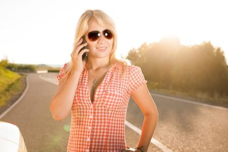 girl phones beside a car