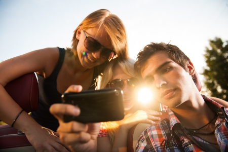 friends looking at a video on car Stock Photo