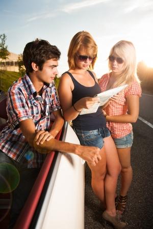 fiends beside a car studying a roadmap