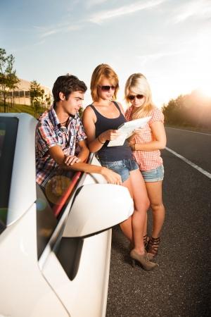 roadmap: fiends beside a car studying a roadmap