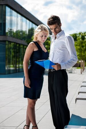 architectural survey: Businessman with board explaining a female colleague a project