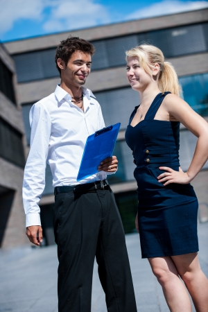 Businessman with board explaining a female colleague a project