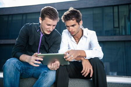 Two businessmen discuss a project on a tablet computer Stock Photo - 17718296