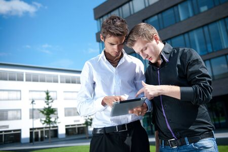 Two businessmen discuss a project on a tablet computer Stock Photo - 17718373