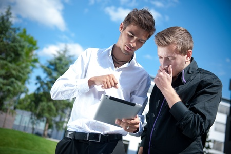 Two businessmen discuss a project on a tablet computer