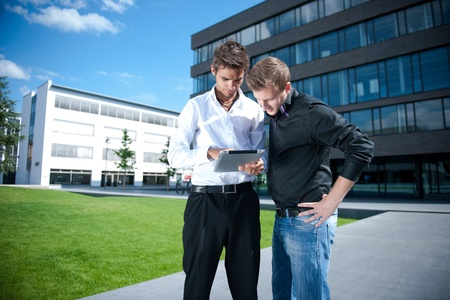 Two businessmen discuss a project on a tablet computer Stock Photo - 17718326