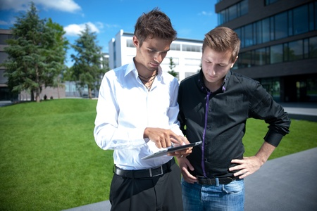 architectural survey: Two businessmen discuss a project on a tablet computer