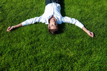 stressed out business man relaxing on a green meadow