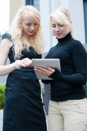 Businesswomen in front of a building holding a tablet computer photo