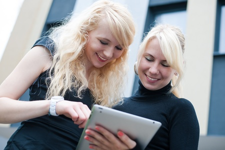 Businesswomen in front of a building holding a tablet computer Stock Photo