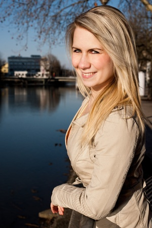 young woman stands on the railing smiling Stock Photo