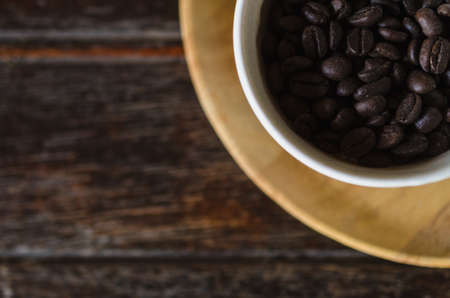 wooden insert: Top view of coffee beans in a cup on wooden background. For insert text design in advertising.