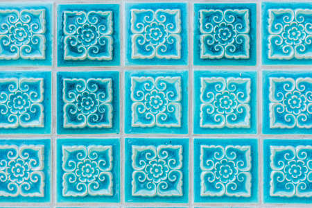 weatherworn: Pattern of turquoise flower glazed tiles. Abstract Background.