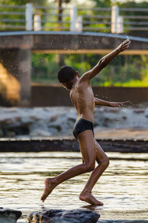 Action of a boy before jumping into the water, in Thailand. Motion Blur.