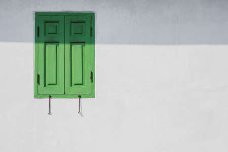 window shade: Green window on a white wall with shade from eaves. You can fill idea or text into space. Stock Photo