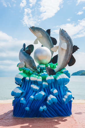 lively: Lively fish and pearl statue on the shore with blue sky, in Thailand. Stock Photo