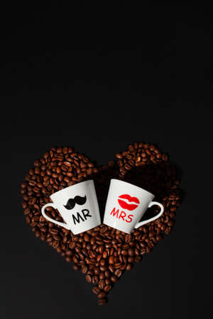 Espresso coffee cups with coffee beans on black background. Romantic mood card, valentines day. Top view.