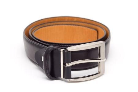 Leather belt with a metal buckle. Isolated on a white background. A shade below. photo